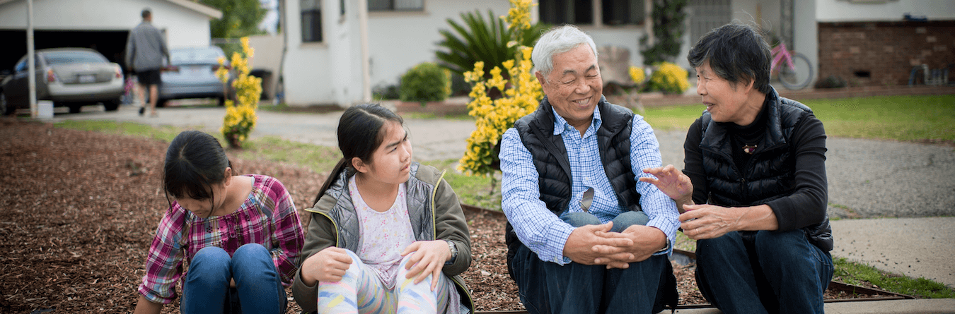seniors talking on curb with two children