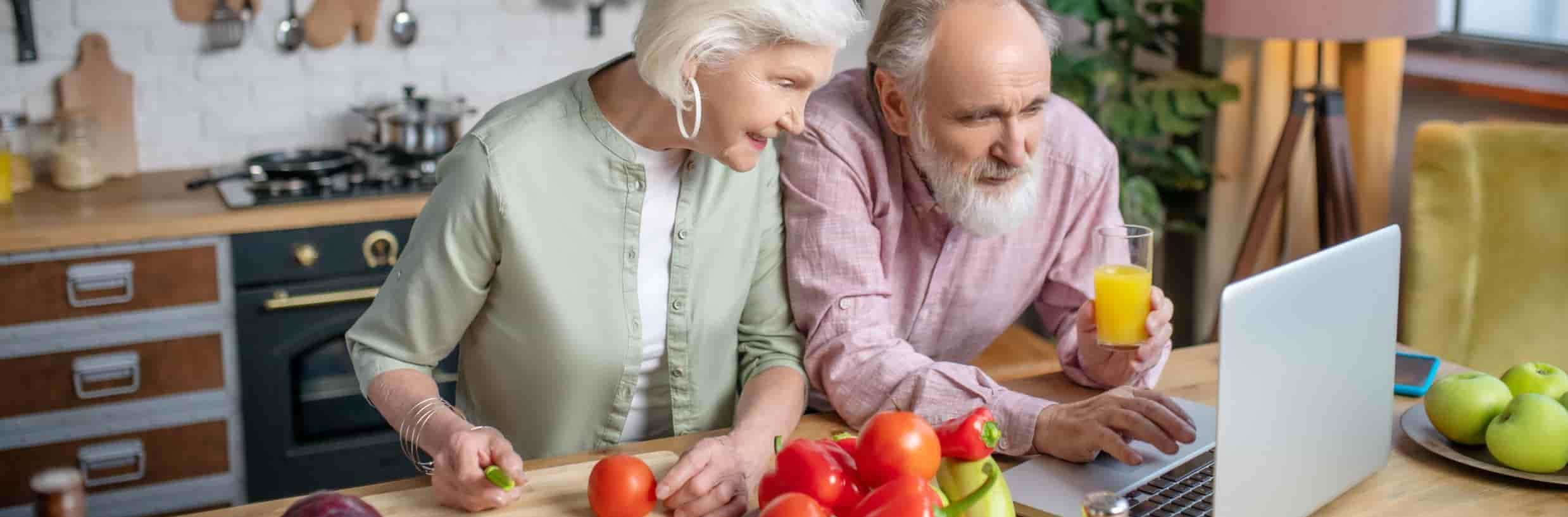 Elderly couple looking up recipes on their computer